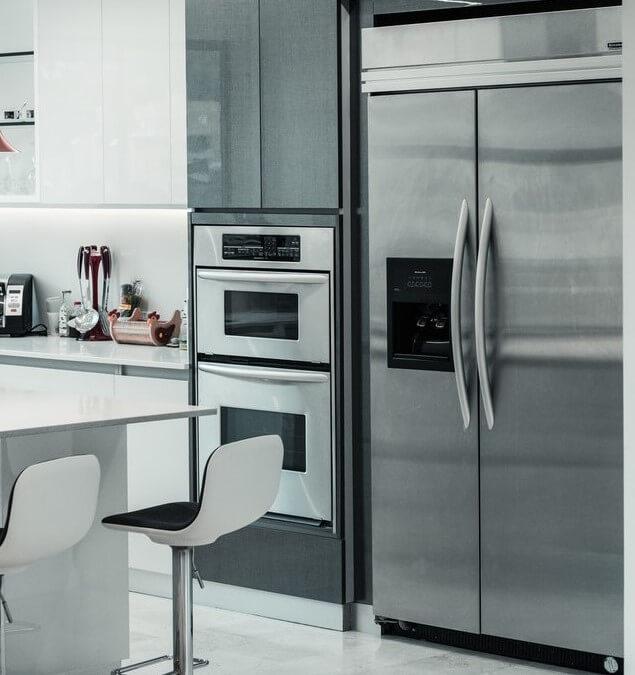 frigider si cuptor din aluminiu otel stainless steel in bucatarie moderna cu masa eleganta si scaune albe